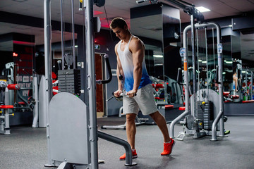 young muscular sporty man doing exercises in gym