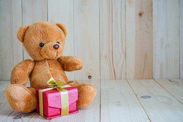 bear doll and red gift box on the wood floor , select focus eye
