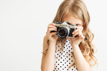 Portrait of a lovely little girl with old SLR film camera