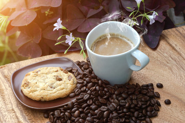 Coffee and cookie on a wood background.