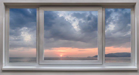 A window with the panoramic views of the sea and the beautiful sunrise