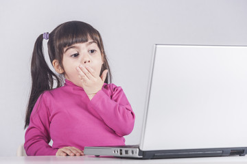 Little girl reacts while using a laptop. Internet safety concept.