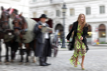 Woman in street with horses and coach