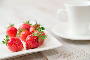 Ripe strawberry fruits on a white plate