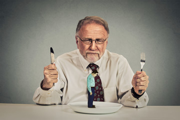 businessman with knife and fork looking at his employee on a plate
