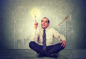 Handsome middle aged business man pointing at light bulb. Executive thinking over his strategy