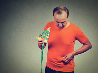 Middle aged man with slice of pizza measuring tape and overweight abdomen.