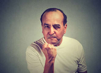 Middle aged angry man with fist up isolated on gray wall background