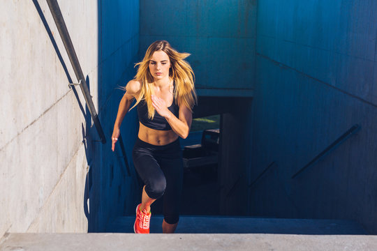 Female athlete running fast up the stairs