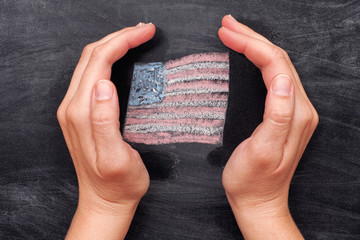 Hands protecting drawn Usa flag on black chalkboard background
