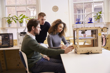 Team Of Designers Working With 3D Printer In Design Studio