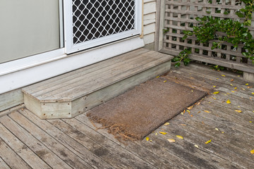 Old plain coir doormat placing in front of the doorstep at back door during Autumn