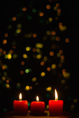 Candles burning with colorful bokeh lights