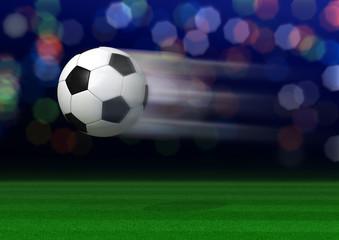 geschossener Fußball über Rasen im Stadion