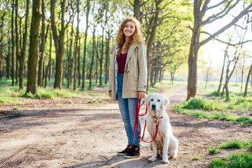 beautiful young girl walking with labrador dog in park