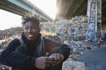 Smiling young man sitting under the bridge