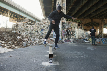 A young man skateboarding.