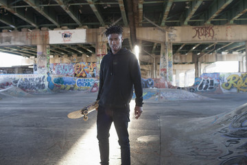 Portrait of young man standing under bridge at skate park