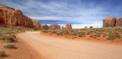 scenic and empty dirt road in monument valley