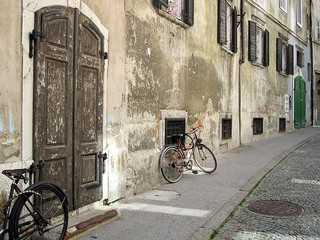 Old vintage picture with rusty grey wall and two bicycles