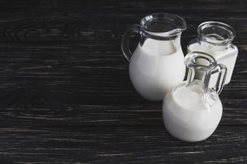 Milk jars on wooden background