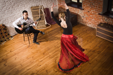 Photo sur Aluminium Carnaval Young woman dancing flamenco and a man playing the guitar