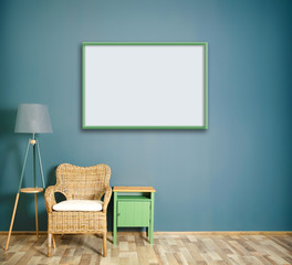 Wicker chair and empty picture frame on blue wall background