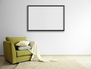 Green armchair and empty picture frame on light wall background