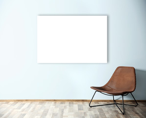 Comfortable chair and empty picture frame on blue wall background