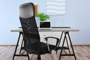 Modern workplace with office chair and laptop