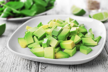 Fototapete - Cubes of fresh avocado on plate closeup
