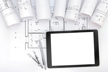 architect workspace with blueprint rolls, tablet and drawing ins