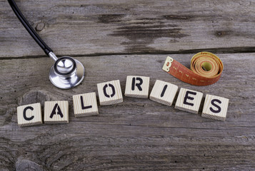 Text: CALORIES from wooden letters on wooden background.