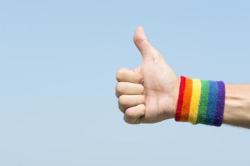 Hand of athlete giving thumbs up with gay pride rainbow colors wristband against bright blue sky