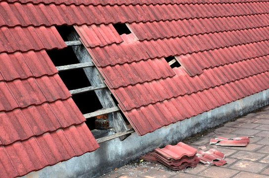 Destroyed roof tiles by strong wind.