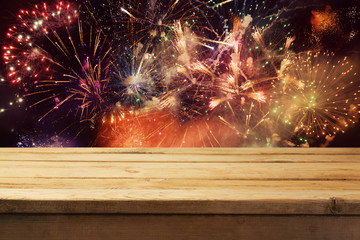 4th of July fireworks background with empty wooden table. Independence day of America celebration
