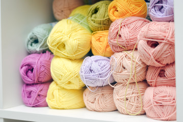 Colorful balls of wool or cotton yarn piled up on shop shelf