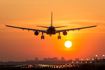 Tuinposter Passenger plane is landing during a wonderful sunrise.