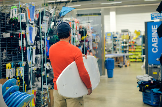 Male surfer choosing holding a surf board on shop background