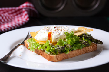 Toasted sandwich with salad leaves, asparagus, cheese and poached egg, closeup
