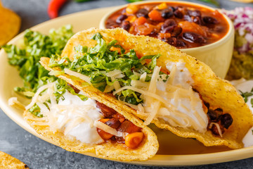 Tacos with chili con carne, salad, cheese and sour cream.