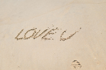 Love U sign on the sand beach copy space background texture
