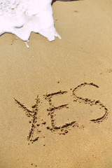Yes sign written in sand on beach texture sunny background