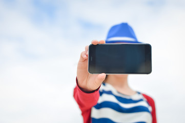 Closeup on hand holding smart phone, blue sky white clouds background outdoors