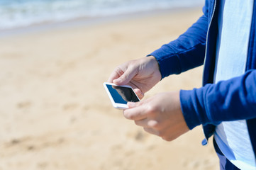 Back view shot of man holding smartphone photographing selfie or beach background