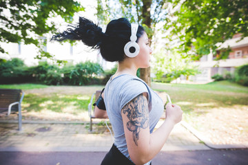 Half length profile of a sportive young mixed race curly black hair woman running in a park, listening music with headphones - healthy, fitness, sport concept