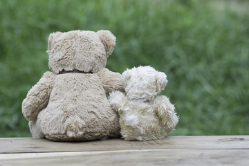 Two teddy bears sitting back on the wooden floor.