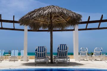 Liegen mit Strohsonnenschirm am karibischen Strand in Kuba