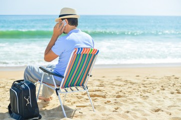 Man chilling on the beach talking on smartphone. Back side view of guy enjoying outdoors background