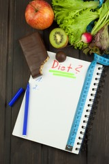 Preparing for the diet program. The decision to initiate dieting. Planning of diet. Notebook measuring tapes and pen on wooden table.